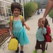 Iowa Montessori school preschoolers walking in to school with their backpacks on.