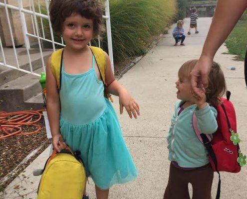 Iowa Montessori school preschoolers walking in to school with their backpacks on.